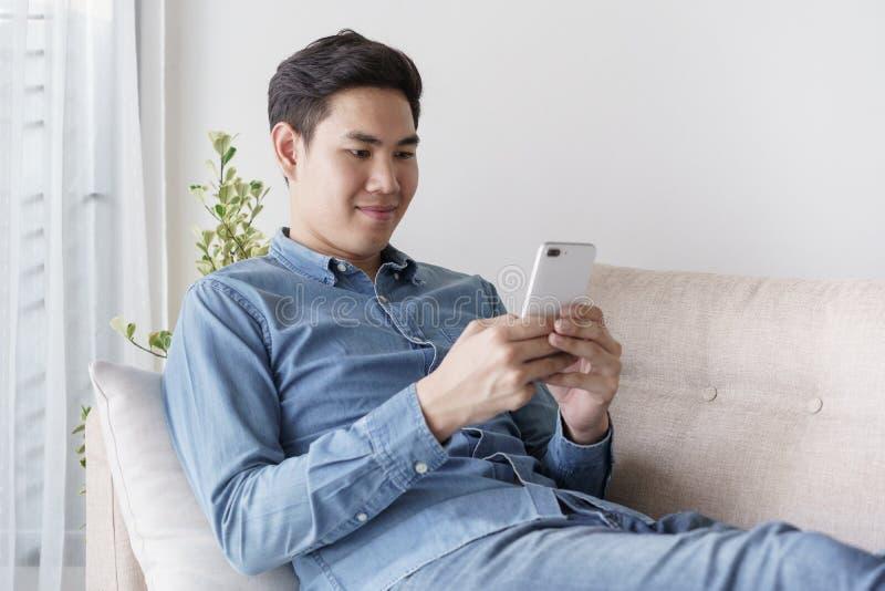 Portrait de jeune homme utilisant la chemise bleue regardant avec le smartphone et se reposant ? son sofa dans le bureau photos stock