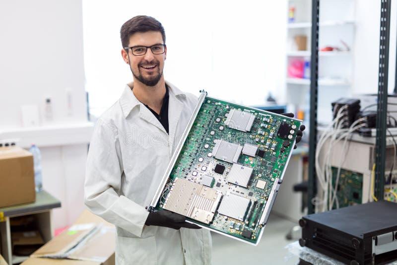 Portrait de jeune ingénieur tenant la carte de CMTS photo stock