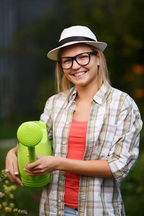 Portrait de jeune jardinier féminin heureux avec la boîte d'arrosage verte image stock