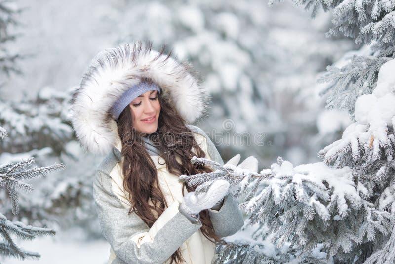 Portrait de jeune jolie femme dans vêtements blanc-gris avec les yeux fermés dans la forêt d'hiver photo libre de droits