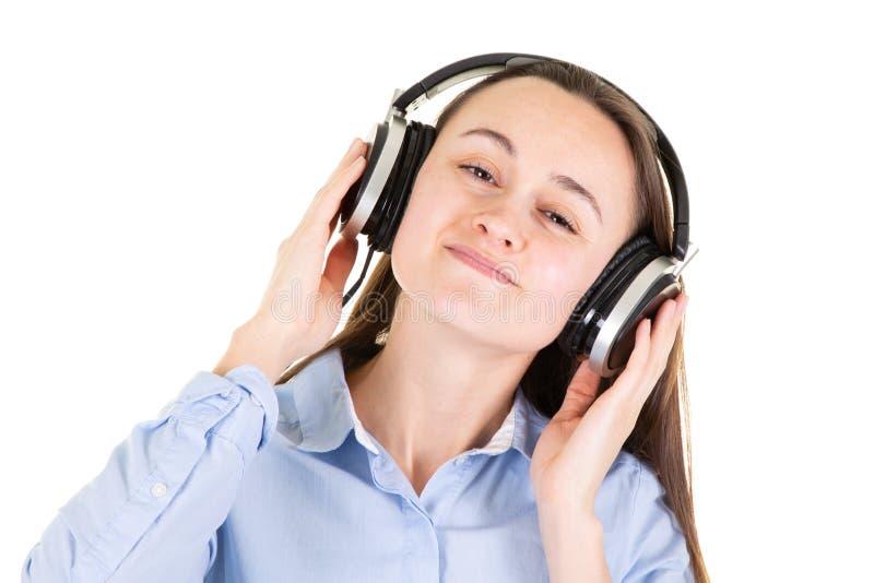 Portrait de jeune jolie femme riante dans la musique de écoute d'écouteurs images libres de droits