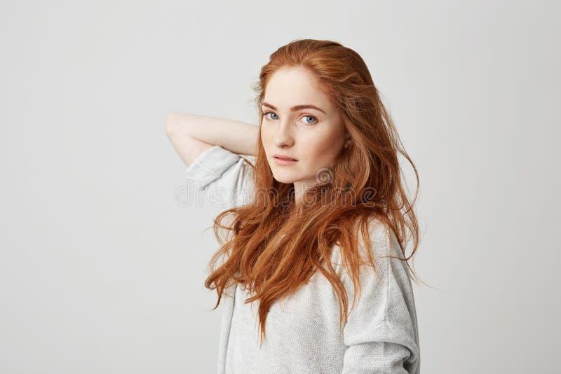 Portrait de jeune jolie fille de gingembre avec des taches de rousseur regardant les cheveux émouvants d'appareil-photo au-dessus photo stock