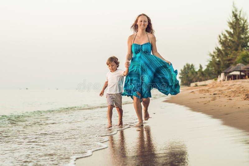 Portrait de jeune mère de sourire avec le petit enfant courant sur le Th photo stock
