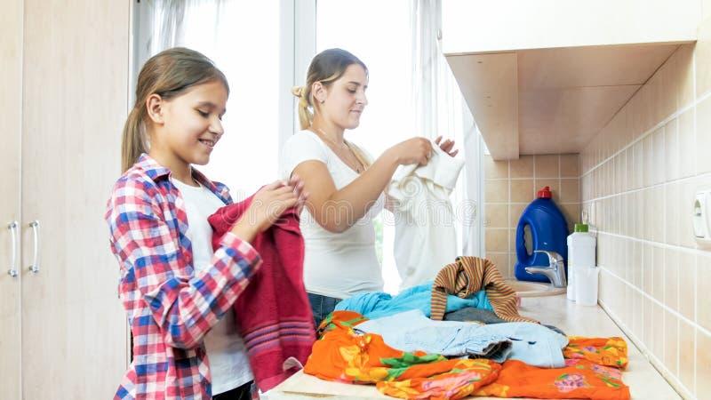 Portrait de jeune mère de sourire avec les vêtements se pliants de fille adolescente après blanchisserie photos stock