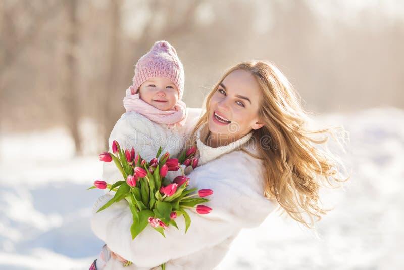 Portrait de jeune mère de sourire avec un bébé dans mains pendant le jour ensoleillé d'hiver images libres de droits