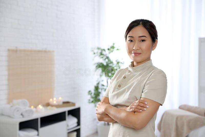 Portrait de jeune masseuse asiatique dans le salon de station thermale photographie stock libre de droits