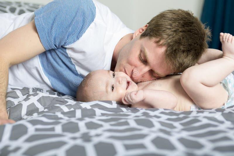 Portrait de jeune père heureux avec un bébé dans le lit à la maison photos libres de droits