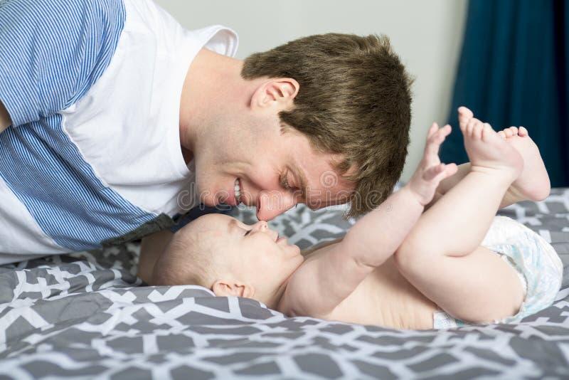 Portrait de jeune père heureux avec un bébé dans le lit à la maison image stock