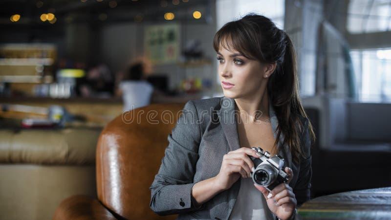 Portrait de jeune photographe d'adolescent avec de longs cheveux dans le T-shirt noir en café Belle fille tenant le vieil apparei image libre de droits