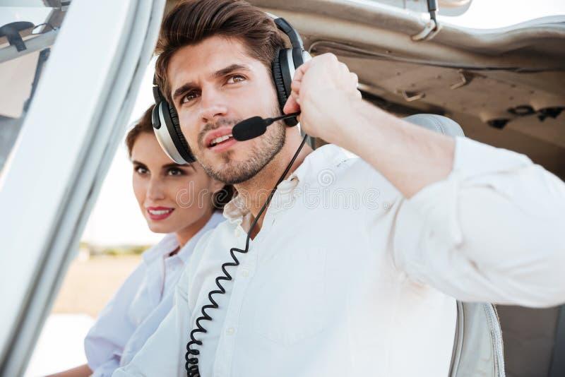 Portrait de jeune pilote et de belle hôtesse à l'intérieur de carlingue d'avion photos stock
