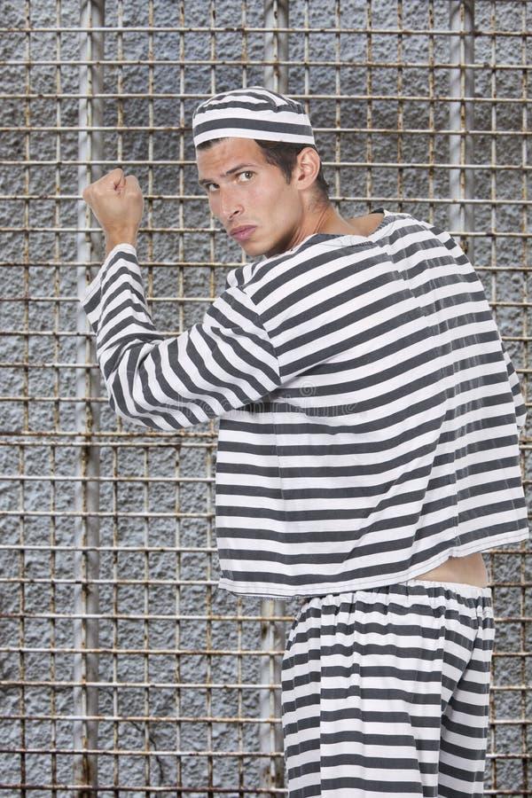 Portrait de jeune prisonnier masculin dans l'uniforme se tenant contre la cellule de prison photo libre de droits