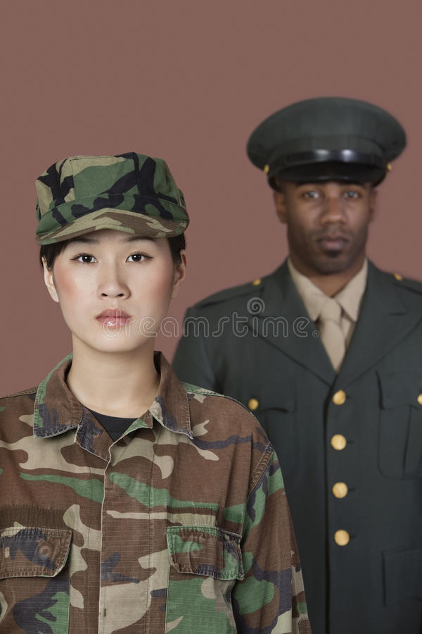 Portrait de jeune soldat des USA Marine Corps de femelle avec le dirigeant masculin à l'arrière-plan photos stock