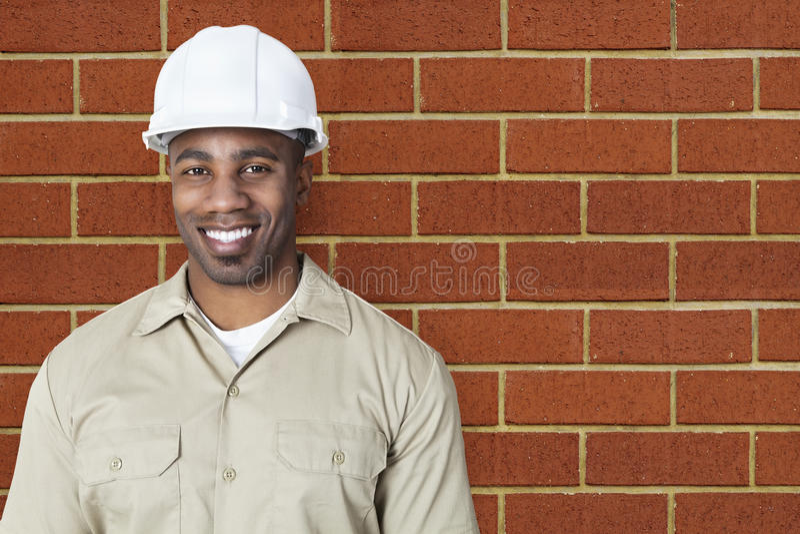 Portrait de jeune travailleur de la construction heureux avec le masque au-dessus du mur de briques photographie stock