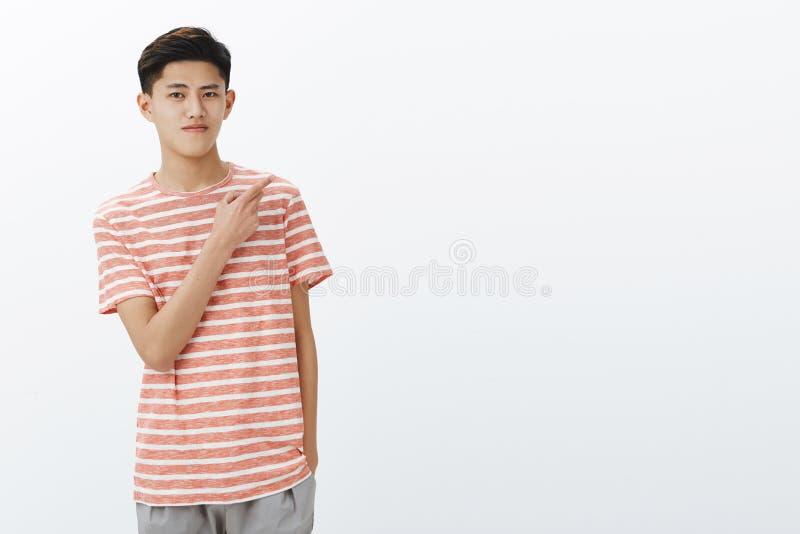 Portrait de jeune type asiatique adolescent attirant calme avec la coiffure courte foncée dans le T-shirt rayé tenant la main dan image libre de droits