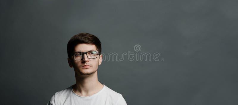 Portrait de jeune type songeur d'adolescent au-dessus de fond noir photos stock