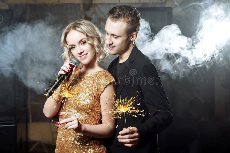 Portrait de jeunes ajouter heureux aux cierges magiques chantant avec le microphone photo stock