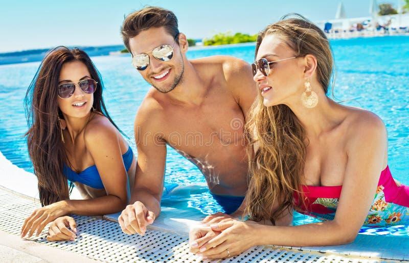 Portrait de jeunes amis dans la piscine photo stock