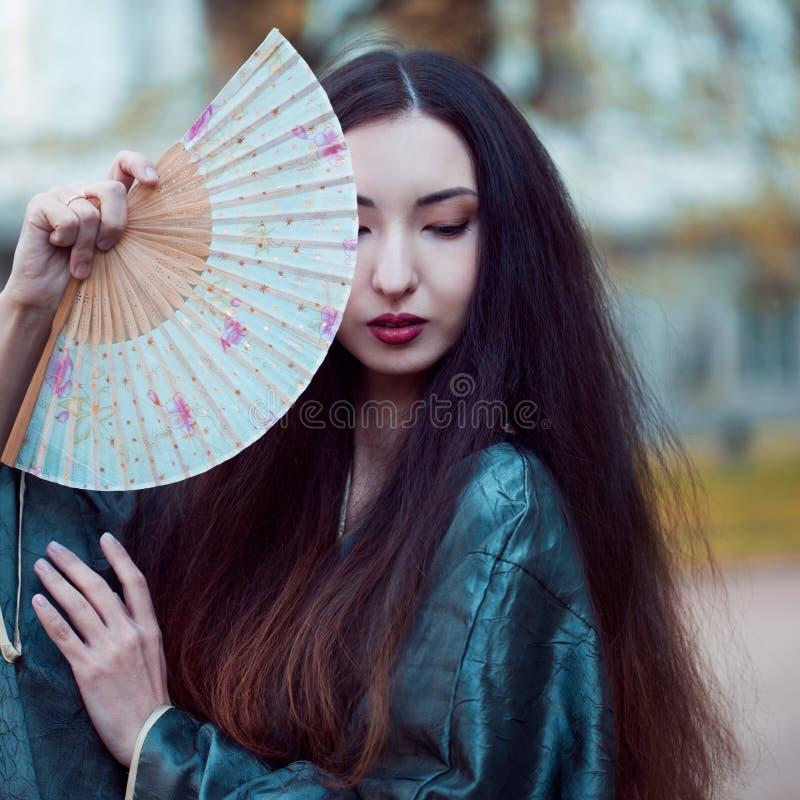 Portrait de jeunes beaux Asiatiques dans le kimono gris et avec une fan images libres de droits