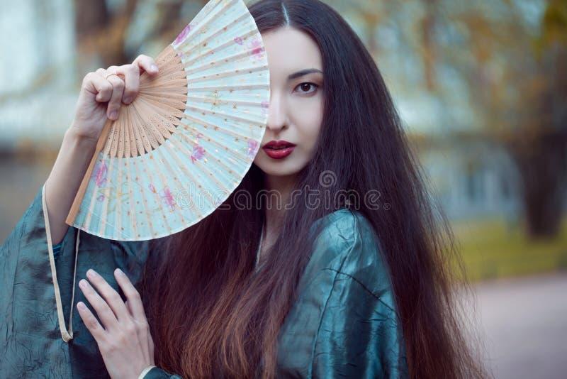 Portrait de jeunes beaux Asiatiques dans le kimono gris et avec une fan image stock