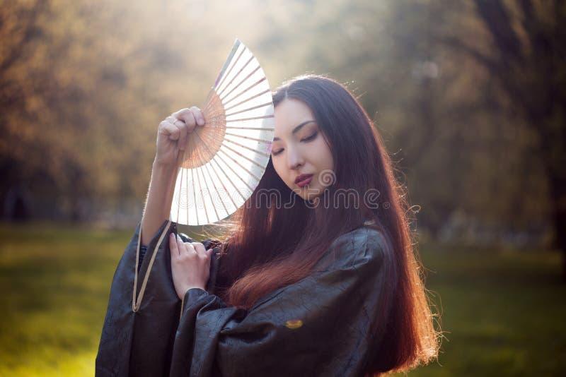 Portrait de jeunes beaux Asiatiques dans le kimono gris et avec une fan photos libres de droits