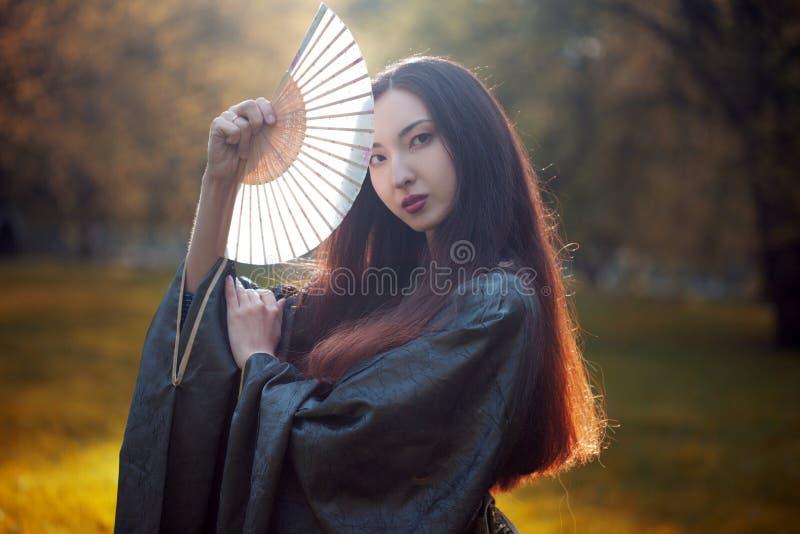 Portrait de jeunes beaux Asiatiques dans le kimono gris et avec une fan photographie stock libre de droits