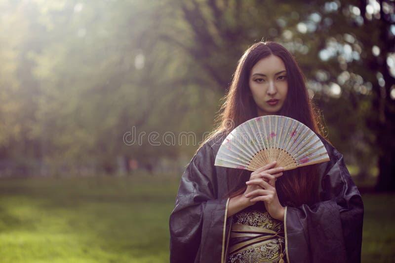 Portrait de jeunes beaux Asiatiques dans le kimono gris et avec une fan photos stock