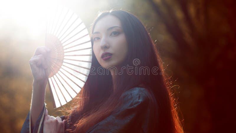 Portrait de jeunes beaux Asiatiques dans le kimono gris et avec une fan, extérieur photographie stock