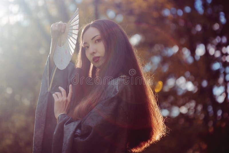 Portrait de jeunes beaux Asiatiques dans le kimono gris et avec une fan, extérieur photo libre de droits