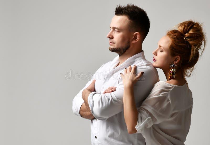 Portrait de jeunes couples élégants dans des vêtements officiels se tenant sur le fond gris image stock