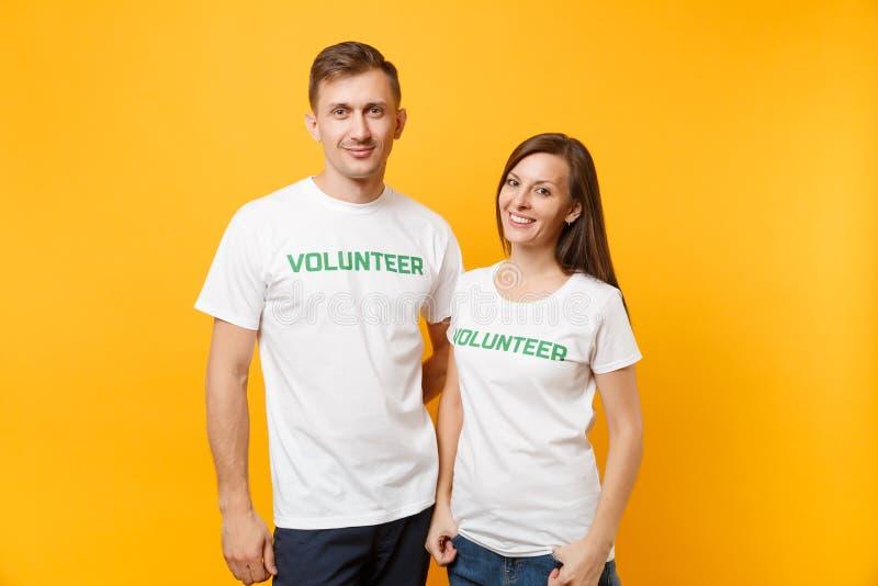 Portrait de jeunes couples de collègues dans le T-shirt blanc avec le volontaire écrit de titre de vert d'inscription d'isolement photographie stock