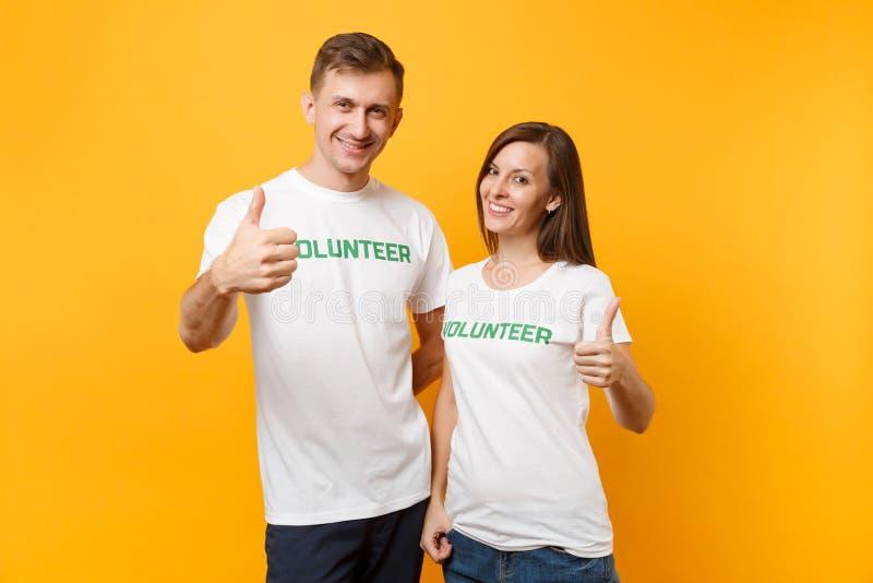 Portrait de jeunes couples de collègues dans le T-shirt blanc avec le volontaire écrit de titre de vert d'inscription d'isolement photographie stock libre de droits