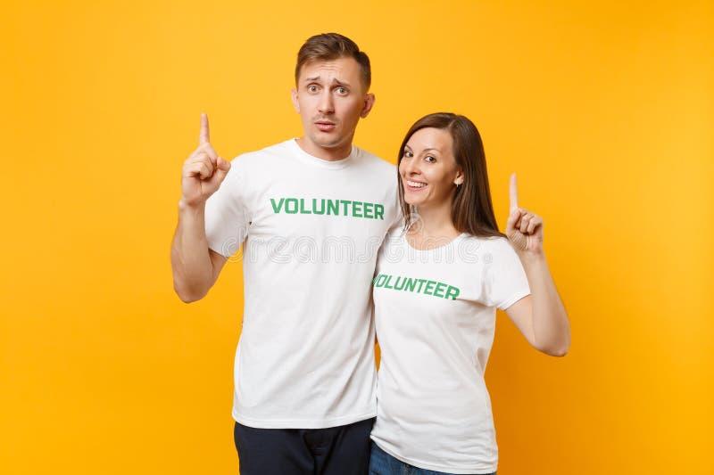 Portrait de jeunes couples de collègues dans le T-shirt blanc avec le volontaire écrit de titre de vert d'inscription d'isolement photo stock