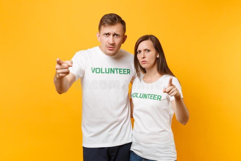 Portrait de jeunes couples de collègues dans le T-shirt blanc avec le volontaire écrit de titre de vert d'inscription d'isolement photos libres de droits
