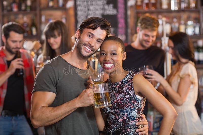 Portrait de jeunes couples embrassant tout en tenant des tasses de bière photographie stock libre de droits