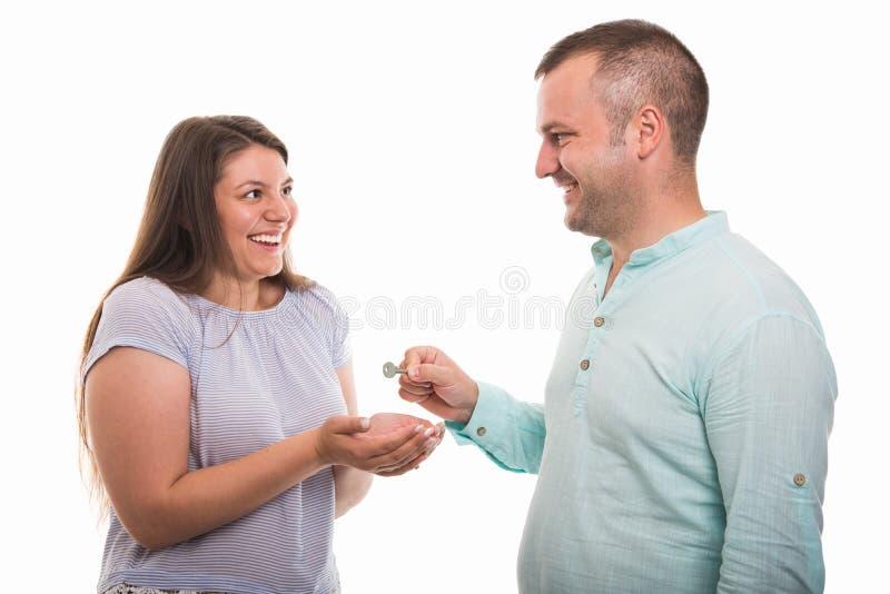 Portrait de jeunes couples heureux donnant la clé de maison photographie stock libre de droits