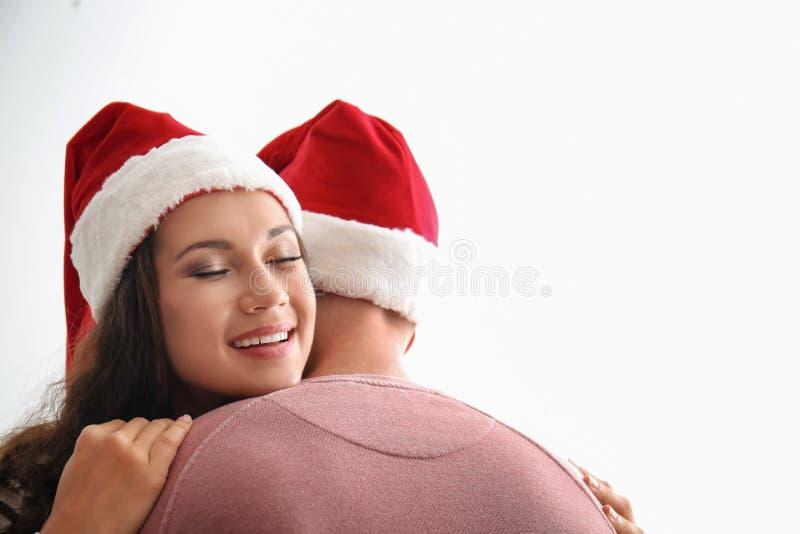 Portrait de jeunes couples mignons dans des chapeaux de Santa étreignant sur le fond blanc image stock