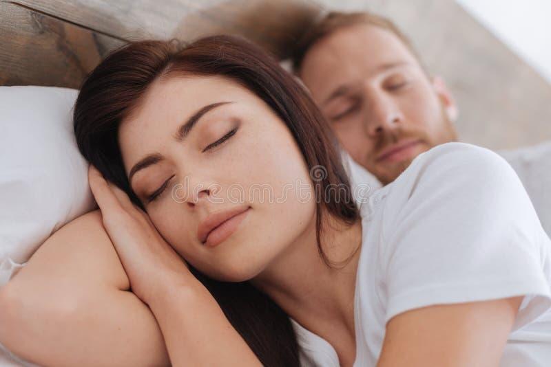 Portrait de jeunes couples romantiques dormant dans le lit image stock