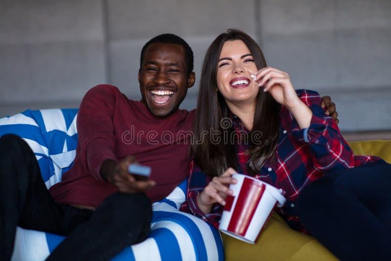 Portrait de jeunes couples se reposant sur le sofa observant un film avec l'expression sur leurs visages image libre de droits