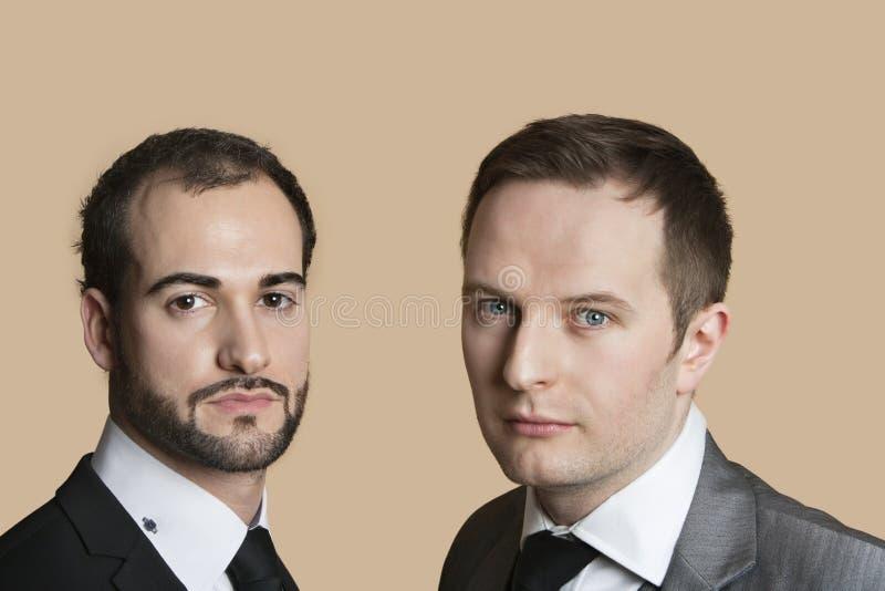 Portrait de jeunes hommes d'affaires au-dessus de fond coloré photographie stock libre de droits