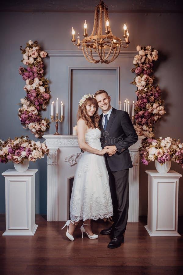 Portrait de jeunes jeunes mariés heureux dans un intérieur classique près de la cheminée avec des fleurs Jour du mariage, thème d photo stock
