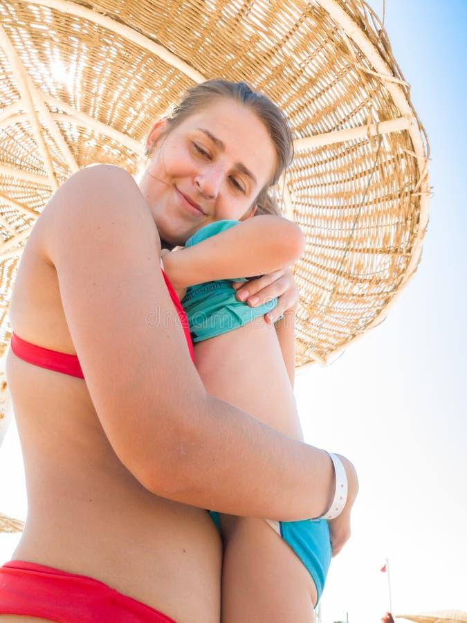 Portrait de jeunes soins et de mère affectueuse étreignant son peu de fils sur la plage de mer sous le parapluie de paille photographie stock libre de droits