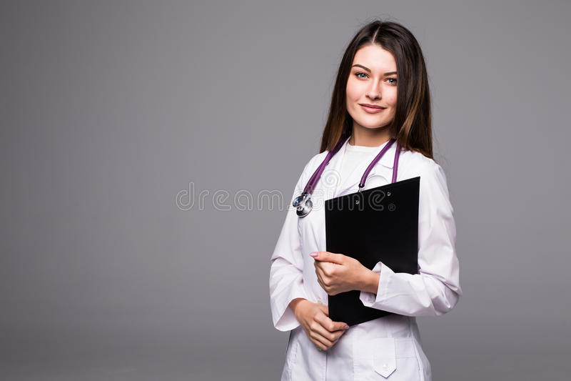 Portrait de joli docteur heureux de jeune femme avec le presse-papiers et le stéthoscope au-dessus du fond blanc photo stock