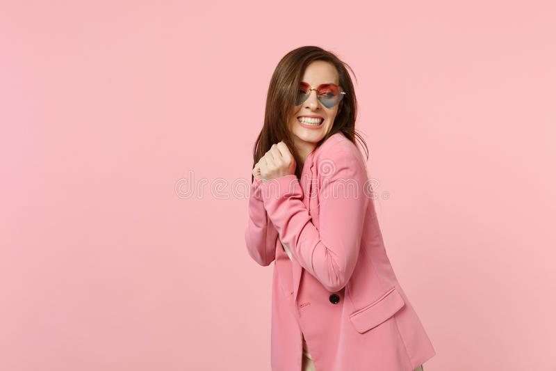 Portrait de jolie belle jeune femme de sourire en verres de coeur se tenant, regardant de côté d'isolement sur le rose en pastel images libres de droits