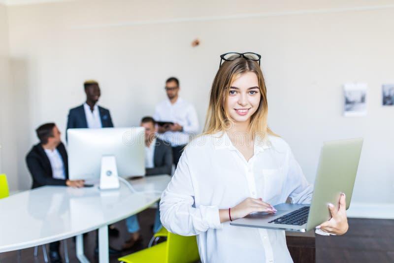 Portrait de jolie femme gaie d'affaires dans un ordinateur portable de participation d'environnement de bureau photo stock