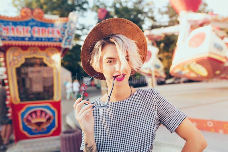 Portrait de jolie fille blonde avec la coupe de cheveux courte posant en parc d'attractions Elle porte la robe à carreaux, chapea image stock