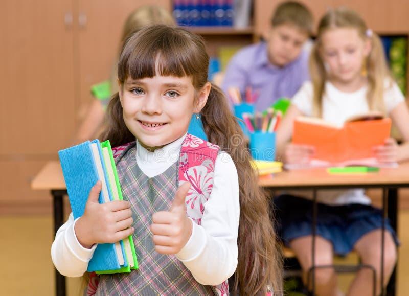 Portrait de jolie fille préscolaire avec des livres dans la salle de classe montrant le pouce  photographie stock