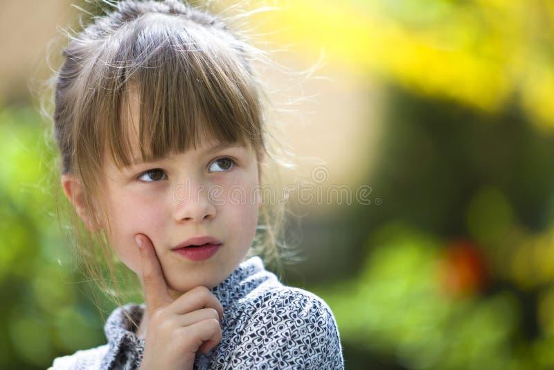 Portrait de jolie fille réfléchie mignonne d'enfant dehors sur le fond lumineux coloré ensoleillé brouillé photos stock