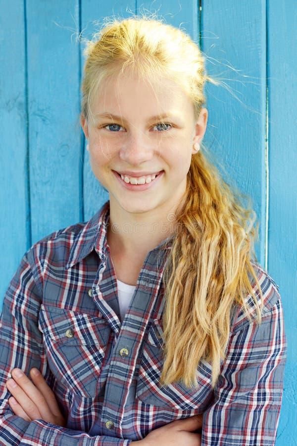 Portrait de jolie fille sur le fond en bois bleu de mur photos stock