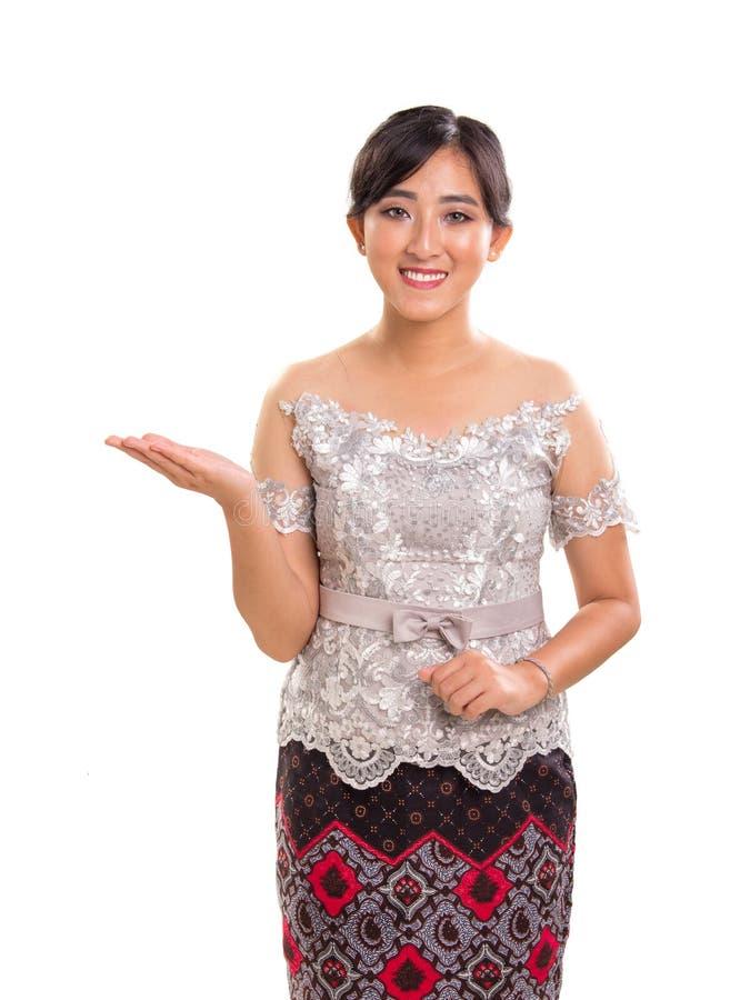 Portrait de kebaya de port de sourire amical de fille asiatique du sud-est et costume de batik donnant la manière de côté de dire images stock
