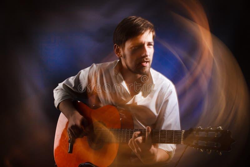 Portrait de l'âme du musicien qui joue la guitare acoustique et chanson émotive de chant Barde célèbre photographie stock libre de droits